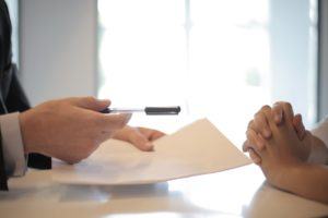 Close up image of a person handing a document and pen for another person to sign